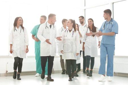 Photo pour De jeunes médecins traversant le couloir de l'hôpital. photo avec espace pour le texte - image libre de droit
