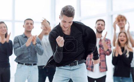 Photo pour Leader jubilant debout devant l'équipe d'affaires. concept de succès - image libre de droit