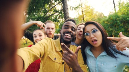 Photo for Point of view shot of joyful friends taking selfie in park looking at camera, making funny faces and laughing having fun. Modern technology, friendship and nature concept. - Royalty Free Image