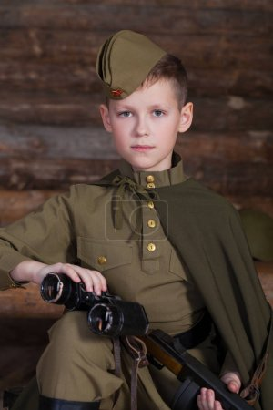Russian boy in the old-fashioned Soviet military uniform with a binoculars on the background of a dugout from the bars