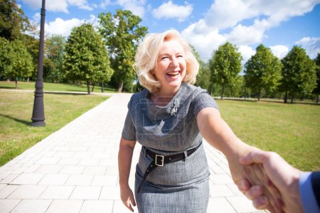 Photo for Follow me. Portrait of lovely middle aged blonde woman in the summer park - Royalty Free Image