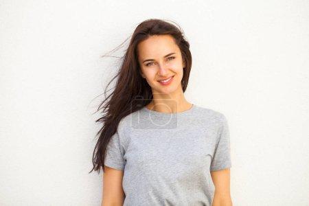 Photo pour Joyeux Belle femme brune en t-shirt gris, isolé sur fond de mur blanc - image libre de droit