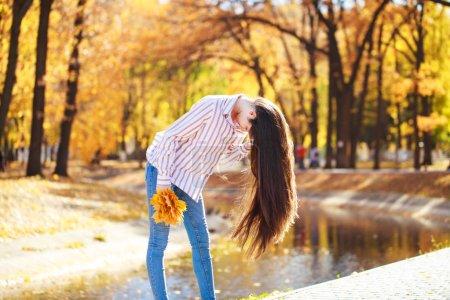 Photo pour Fille heureuse de brunette posant dans le fond de parc d'automne - image libre de droit