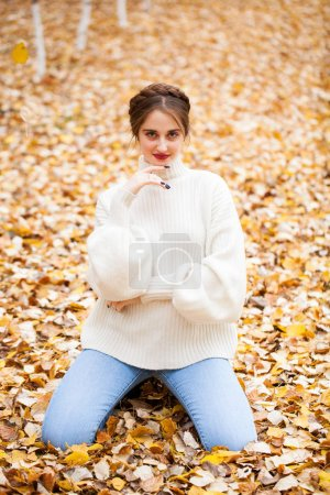 Photo for Portrait of a young beautiful girl in blue jeans and gwhite sweater sits on autumn leaves in a park - Royalty Free Image