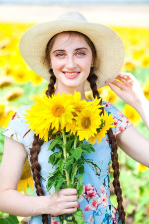 Young beautiful woman in a straw hat in a field of sunflowers