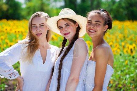 Photo pour Trois belles filles en robes blanches posant sur le fond d'un champ de tournesols - image libre de droit