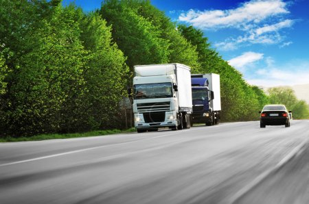 Two trucks with a black car on the coutryside road in motion with green trees against blue sky with clouds
