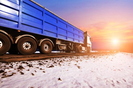 White truck and a blue trailer with space for text on the winter countryside road with snow against blue sky with clouds and bright sunset