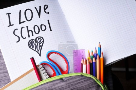 Close-up of full grey school backpack with color pencils, red pen, pink ruler, scissors, notebook and copybook with I Love School sign