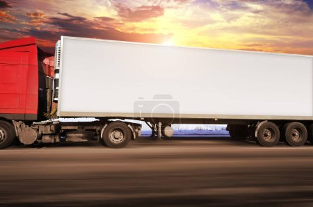 Red truck and white trailer with space for text driving fast on countryside road against sky with sunset