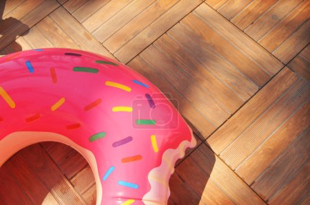 Big inflatable pink donut swimming ring on brown wooden floor