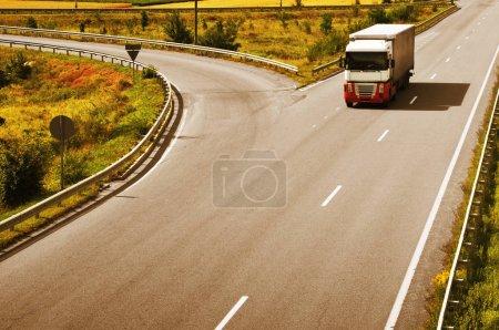 Photo pour Camion blanc et rouge rapide avec remorque grise à la campagne - image libre de droit