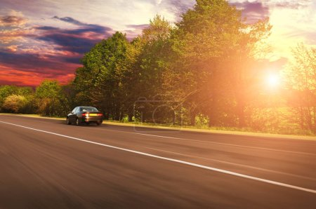 Photo for Black sedan car driving fast on countryside asphalt road with green trees against sky with sunset - Royalty Free Image