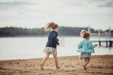 Photo for Two sisters playing on the shore of the lake at summer evening - Royalty Free Image