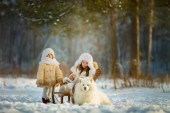 Winter children portrait with samoyed dog