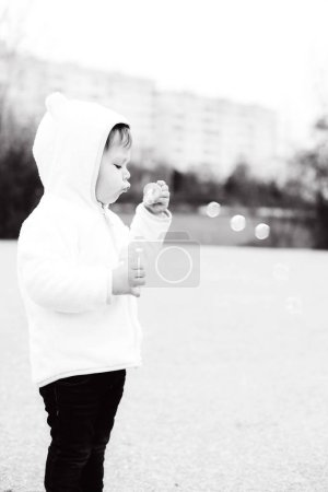 Photo for Cute toddler girl is blowing soap bubbles - Royalty Free Image