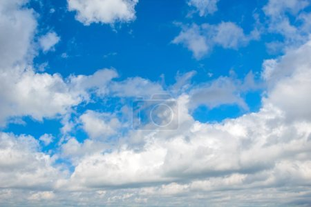 Blue sky with white cumulus clouds background.