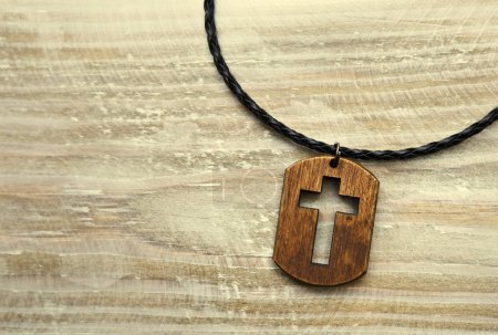 Photo for The cross-shaped pendant on the wooden desk - Royalty Free Image