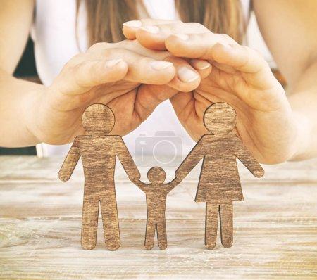 Ręce kobiety chronią drewniane statuetki matki, ojca i