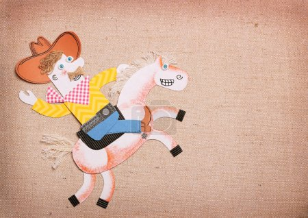 Cowboy in american wild west hat ride a wild horse. Paper cut application rodeo background for text