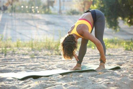 Photo pour Jeune femme Sportswear qui s'étend ses jambes sur le tapis d'yoga en plein air en journée d'été ensoleillée. Fille forme et en santé, faire des exercices de remise en forme. Athlète féminine avec formation de construction musculaire à l'extérieur - image libre de droit