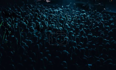 Photo pour Une foule de concerts énorme tourné d'en haut sur le festival de musique dans la discothèque. Grand groupe de jeunes gens faisant la fête sur l'événement de divertissement musical dans le club. Éclairage de couleur vert foncé - image libre de droit