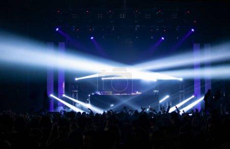 Photo pour Discothèque avec des projecteurs lumineux sur scène.Une foule de fans de musique se sont rassemblés sur la piste de danse pour écouter le décor musical techno dj. - image libre de droit