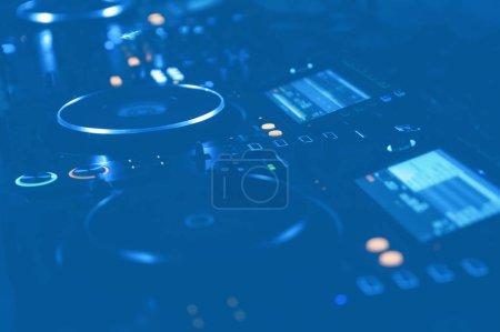 Photo pour Platines tournantes dj professionnelles installées sur scène en lumière bleue.Système de table tournante Hip hop disc jockey sur la fête en boîte de nuit.Festival de musique techno dans un endroit sombre.Équipement audio moderne pour djs - image libre de droit