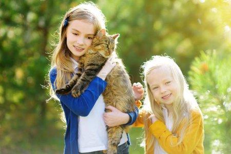 Photo pour Petites filles mignonnes avec leur chat le jour ensoleillé d'automne. Adorables enfants tenant leur chaton de compagnie. Enfants et animaux . - image libre de droit
