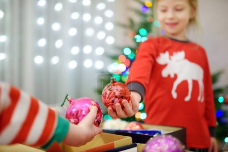 Two adorable sisters decorating a Christmas tree with colorful glass baubles at home. Family leisure at wonderful Xmas time. Trimming a festive tree.