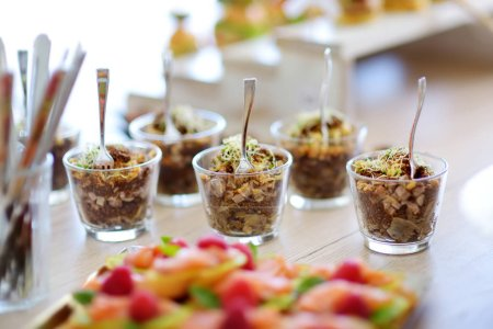 Photo for Fresh and delicious vegetable and pork salad served in mini glasses on a party or wedding reception. Plates with assorted fancy finger food snacks on an event party or dinner. - Royalty Free Image