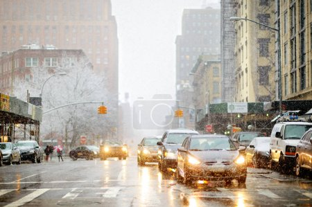 Photo for NEW YORK - MARCH 19, 2015: Cars, taxi cabs and people rushing on busy streets of downtown Manhattan during massive snowfall - Royalty Free Image