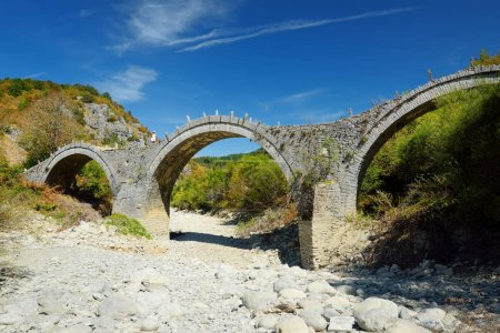 Photo for Plakidas arched stone bridge of Zagori region in Northern Greece. Iconic bridges were mostly built during the 18th and 19th centuries by local master craftsmen using local stone. Epirus, Greece. - Royalty Free Image