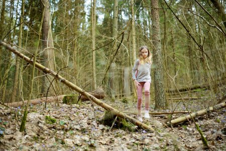 Photo for Cute young girl having fun during forest hike on beautiful early spring day. Active family leisure with kids. Family fun. - Royalty Free Image
