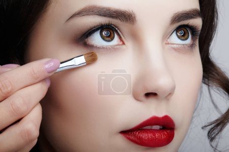 Photo for Close up portrait of beautiful young brunette woman face. Female applying mascara to eyelashes by makeup brush - Royalty Free Image