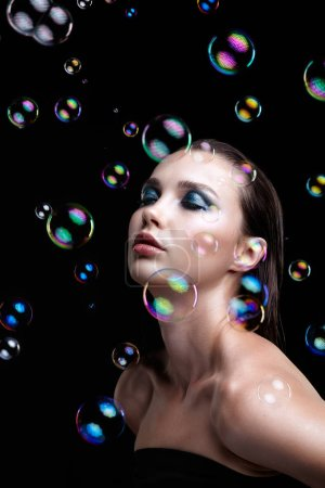 Beautiful young brunette woman with soap bubbles on black background. Female with eyes closed.