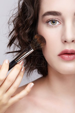 Photo for Make-up artist apply beauty makeup on the face of a beautiful girl. Visagist with makeup brush in hand. - Royalty Free Image
