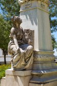 Statue of woman sitting in front of the plinth of statue of Dr. Barahona Fragoso in the Garden of Diana. Evora. Portugal.