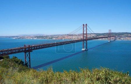 Photo for 25 of April Bridge (Ponte 25 de Abril)  a suspension bridge over Tagus river. The former named Salazar Bridge it was renamed to commemorates the Carnation Revolution. Lisbon. Portugal - Royalty Free Image
