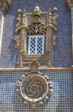 The Neo-Manueline style windows and the Queen Maria II and duke Saxe-Coburg coat of arms between them on the western facade of the New Palace. Pena palace. Sintra. Portugal