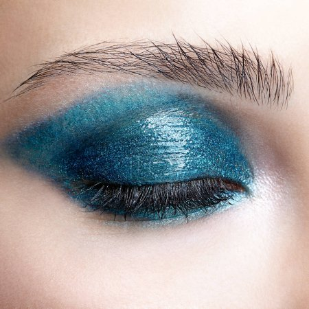 Closeup macro shot of closed human female eye. Woman with natural evening vogue face beauty makeup. Girl with perfect skin and blue-green smoky eyes eye shadows