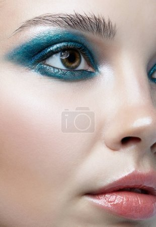 Closeup macro portrait of female face. Woman with evening beauty makeup. Girl with perfect skin and blue-green smoky eyes eye shadows