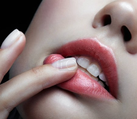Closeup macro portrait of female part of face. Human woman lips with day beauty makeup. Girl with perfect plump  lips shape an finger on lips.
