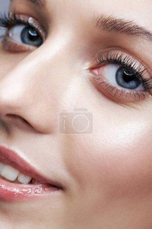 Photo pour Gros coup de macro de sourire visage féminin et maquillage beauté yeux. Femme à la peau blanche brillant paillettes. - image libre de droit