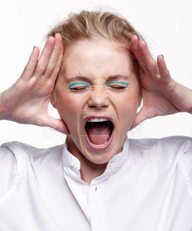 Photo pour Portrait émotionnel d'une jeune femme blonde sur fond gris. Femme mettre les paumes à visage et crier fort - image libre de droit