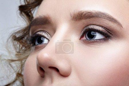 Closeup macro shot of human woman face. Female with smoky eyes makeup