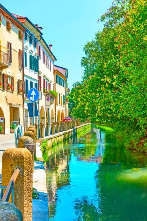 Foto de Edificios antiguos y árboles por canal en Treviso en el verano, Veneto, Italia - Imagen libre de derechos