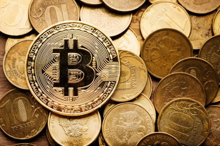 Golden bitcoin and roubles coins, close up view