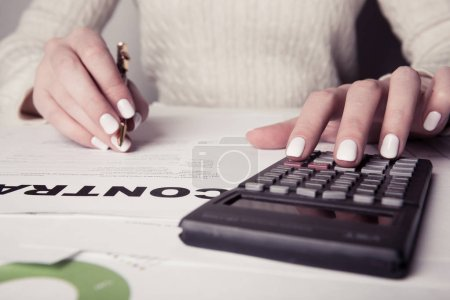 female director working in office , analyzing business statistics, calculator, diagrams and charts on desk