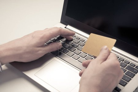 hands of businessman holding credit card and using laptop, e-commerce concept